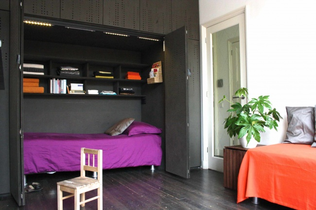 334905-r3l8t8d-650-space-saver-beds-with-purple-bedding-and-built-in-bookshelves-also-cabinets-with-dark-wood-flooring-and-indoor-plant-plus-day-bed-bedding